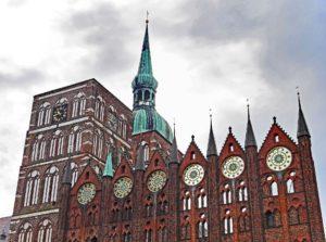 Die Fassade des Stralsunder Rathauses vor den Doppeltürmen der Nikolaikirche